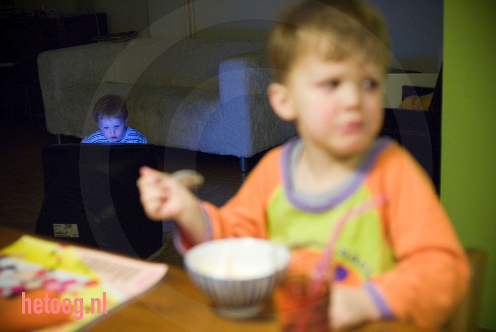 netherlands nederland enschede..peuterkijkt tv terwijl broer tje nog aan het eten is.