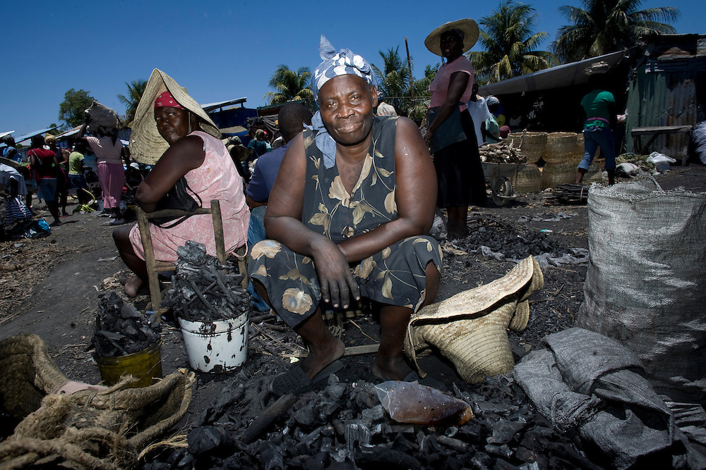 A woman sells charcoal in the market.