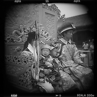 Asia, China, Beijing, Blurred black and white image of young boy crying while posing with family for snapshots wearing Imperial era costumes at photo studio in the Forbidden City