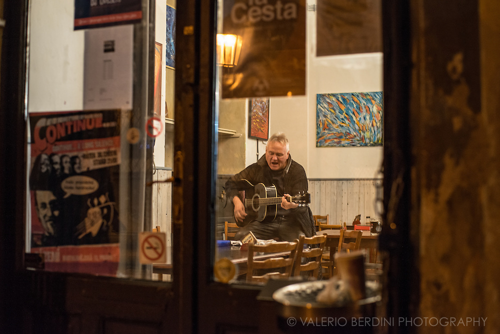 A man sings and plays guitar in an empty bar in central Prague.