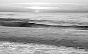 Black and white sunrise over the Atlantic Ocean at Chincoteague NWR, image was taken with a long shutter speed to smooth the wave's motion creating a soft effect