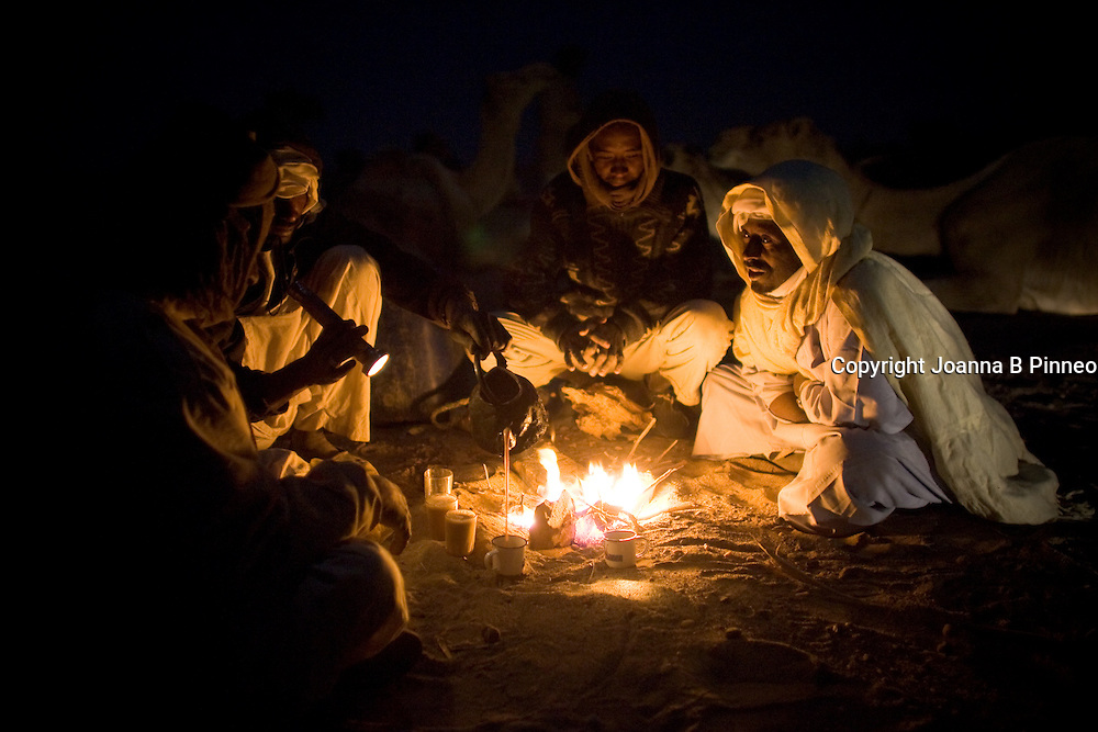 Camel herders gather for dinner in the evening as they travel through the Sahara desert, Sudan on a camel caravan.