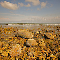 Low tide at Bay of Banderas reviles the stones incrusted with some form of marine life.