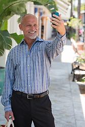 man enjoying taking a selfie while standing on Las Olas Blvd in Fort Lauderdale, Florida