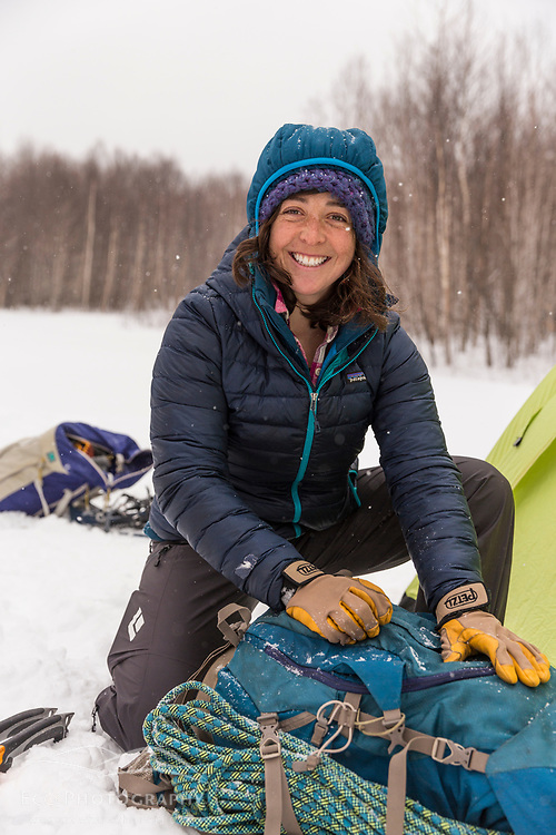 A woman packs her gear while winter camping in New Hampshire's White Mountains. Randolph Community Forest.