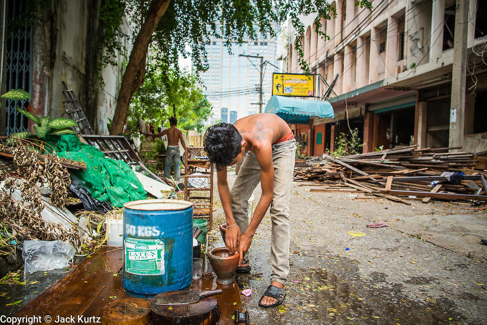 "12 DECEMBER 2012 - BANGKOK, THAILAND:  A worker does his dishes after work on a demolition crew at ""Washington Square"" a notorious entertainment district off Sukhumvit Soi 22 in Bangkok. Demolition workers on many projects in Thailand live on their job site tearing down the building and recycling what can recycled as they do so until the site is no longer inhabitable. They sleep on the floors in the buildings or sometimes in tents, cooking on gas or charcoal stoves working from morning till dark. Sometimes families live and work together, other times just men. Washington Square was one of Bangkok's oldest red light districts. It was closed early 2012 and is being torn down to make way for redevelopment.    PHOTO BY JACK KURTZ"