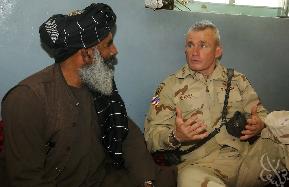 U.S. Army General Dan McNeill (R), Coalition Joint Task Force 180 commander, speaks with the Governor of the Oruzgan province, Jan Mohammed Khan, during a July 7, 2002 personal visit to Tarin Kowt in Southern Afghanistan. McNeill used the visit to speak with Khan about the possibility of stationing more U.S. troops in the region, following an incident last week in which U.S. aircraft mistakenly targeted Afghan civilians celebrating in the nearby village of Deh Rawud.
