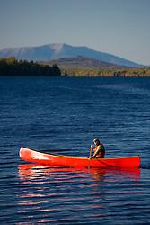 A man paddles his canoe on Seboeis Lake near Millinocket, Maine.  Mount Katahdin is in the distance.