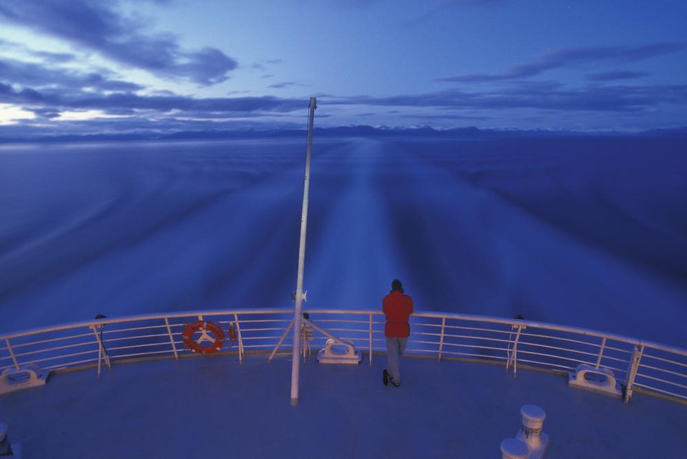 USA, Alaska, (MR) Passenger stands at back rail of Alaska State Ferry at midnight along Inside Passage