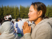 "02 JANUARY 2015 - KHLONG LUANG, PATHUM THANI, THAILAND: A woman prays at Wat Phra Dhammakaya at the start of the 4th annual Dhammachai Dhutanaga (a dhutanga is a ""wandering"" and translated as pilgrimage). More than 1,100 monks are participating in a 450 kilometer (280 miles) long pilgrimage, which is going through six provinces in central Thailand. The purpose of the pilgrimage is to pay homage to the Buddha, preserve Buddhist culture, welcome the new year, and ""develop virtuous Buddhist youth leaders."" Wat Phra Dhammakaya is the largest Buddhist temple in Thailand and the center of the Dhammakaya movement, a Buddhist sect founded in the 1970s.   PHOTO BY JACK KURTZ"