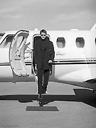 handsome man walking out of a private plane