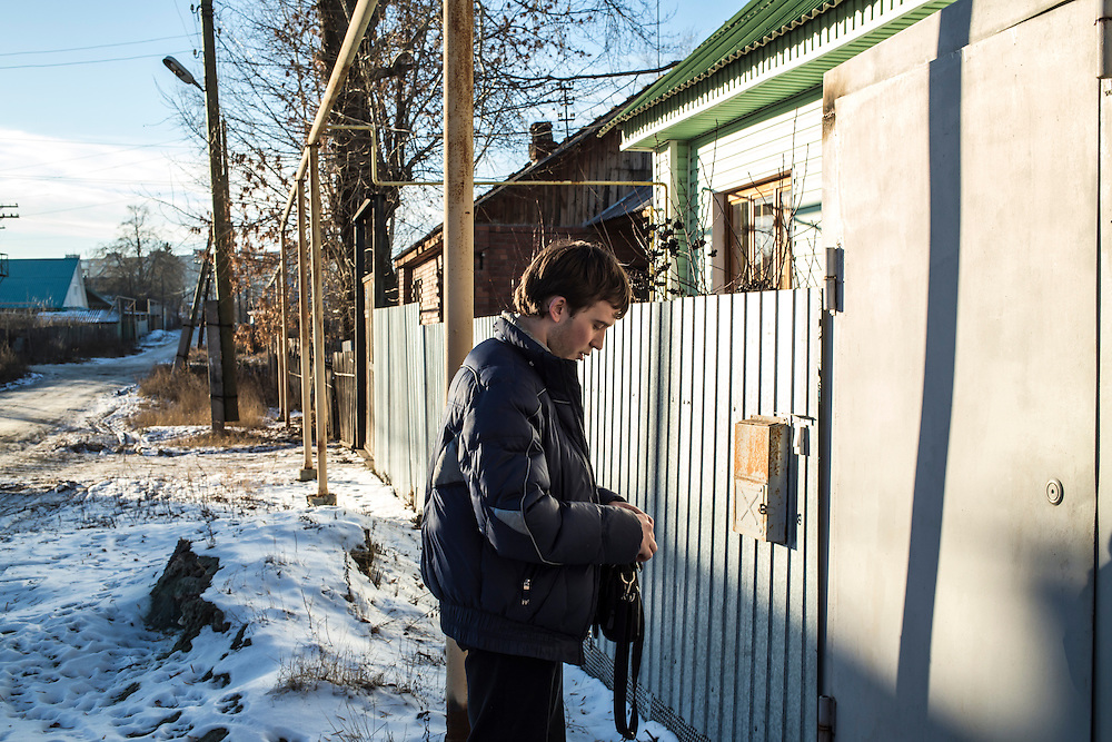 Nikolai Ross locks the gate to his home on Sunday, November 24, 2013 in Asbest, Russia.
