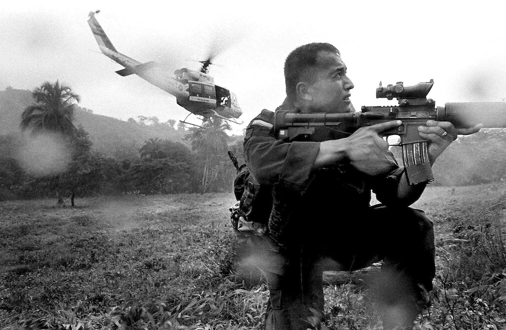 A US trained anti-narcotics police officer crouches on a helicopter landing zone in a rainstorm whilst on an operation against drug traffickers in the Sierra Nevada Mountains, Colombia.