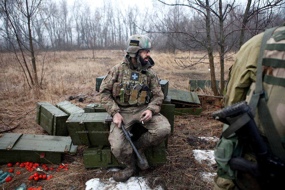 Ben sits on empty ammonition boxes backwards the frontline to talk to his comrades after return from a postion close to the enemy positions.<br />