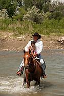 Kennard Real Bird crosses Little Bighorn River with grandson Braxton, Battle of the Little Bighorn Reenactment,  Montana