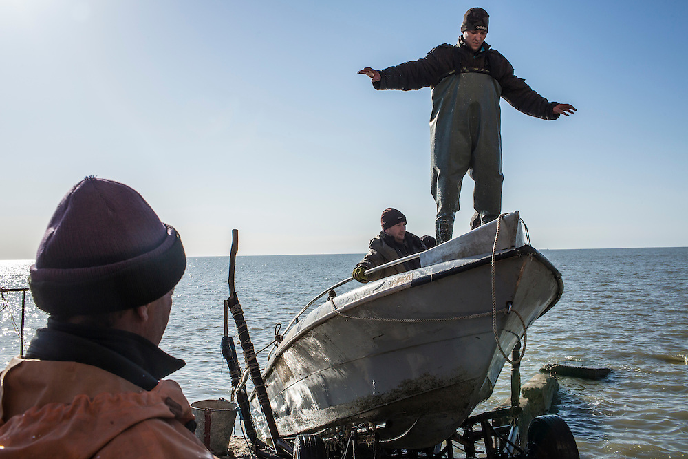 Fishermen return from checking their nets on the Sea of Azov on Saturday, April 11, 2015 in Siedove, Ukraine.