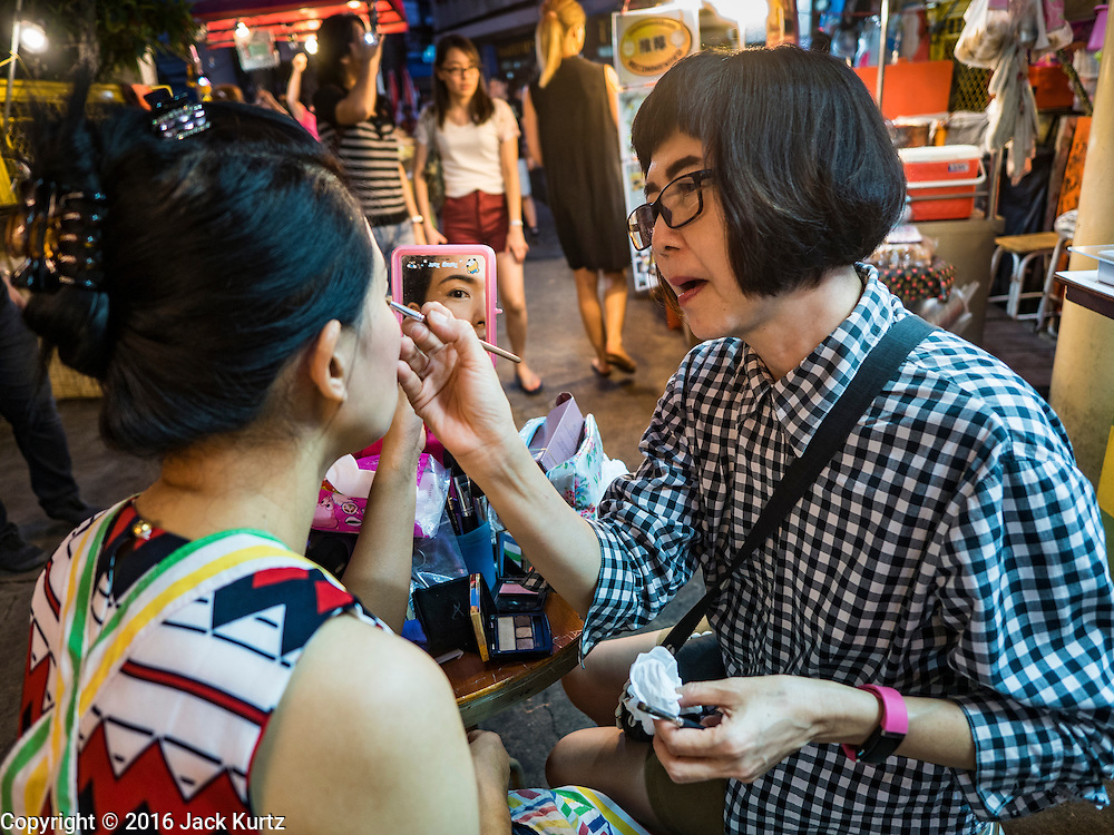 17 JANUARY 2016 - BANGKOK, THAILAND: A food stall vendor gets help with her makeup on Sukhumvit Soi 38, one of the most famous street food areas in Bangkok. The food carts and small restaurants along the street have been popular with tourists and Thais alike for more than 40 years. The family that owns the land along the soi recently decided to sell to a condominium developer and not renew the restaurant owners' leases. More than 40 restaurants and food carts will have to close. Most of the restaurants on the street closed during the summer of 2015. The remaining restaurants are supposed to close by the end of this week.        PHOTO BY JACK KURTZ