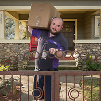 "FedEx driver Gordon Lathrop picks up a package at a house on Cedar Street in Calistoga  ""I've been working with FedEx  four years now...I love getting out every day...and a chance to wear shorts all year 'round."""