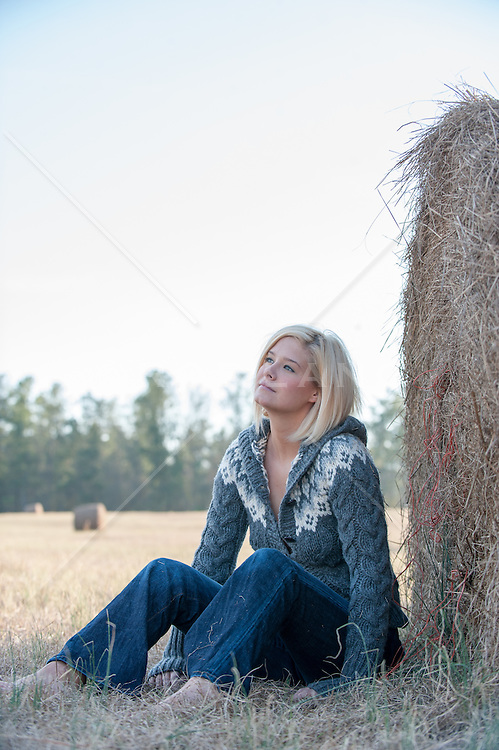 Woman relaxing in a field of hay