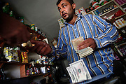 Money exchange in a grocery shop. There&acute;s no bank system anymore available in rebel held areas. But syrian currency is still in regular use for daily needs, though the inflation has trippled the prices. Dollars are beeing used for cross-border deals.<br />