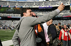 Oct 23, 2011; East Rutherford, NJ, USA; Jimmy Fallon takes a photo of himself with chef Mario Batali before the game between the New York Jets and San Diego Chargers at MetLife Stadium.
