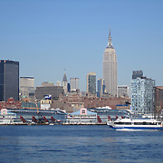 Manhattan skyline as seen from Hoboken, New Jersey. Empire State Building, Chrysler Building, MetLife Building, Chelsea Piers. NY Waterway boat ferrying passengers up the Hudson River!