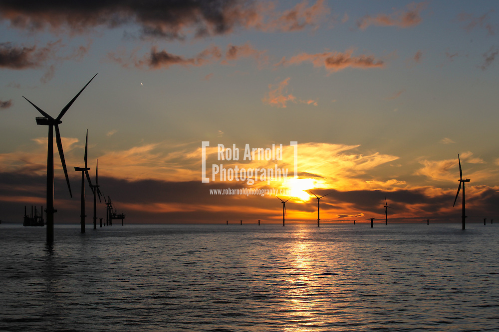 © Rob Arnold.  04/04/2014. North Wales, UK. A bright orange sky at sunset over the Gwynt y Môr Offshore Wind Farm off the coast of North Wales. Photo credit : Rob Arnold