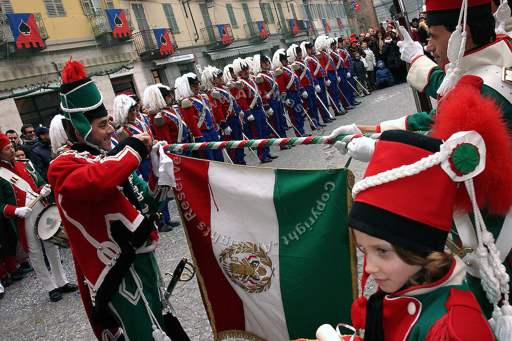 The people of Ivrea, dressed with Napoleonic costumes, are taking part of the opening ceremony of the 4 days celebrations marking the historical Carnival of the town Ivrea, pop. 30.000. During the days of the Carnival, the town becomes crammed with tourists coming to witness the event which finds its roots at the end of the XII Century, when the people led an insurrection against the local tyrant, Count Ranieri of Biandrate, who was exercising the 'jus primae noctis' rule (having the first night) on the local young brides. The battle to overthrow him is represented with a 3-day-fight between factions in which more then 400 tonnes of oranges are thrown. During the celebrations, food stalls, bands playing music, and parades are also present, giving it a typical Medieval atmosphere.