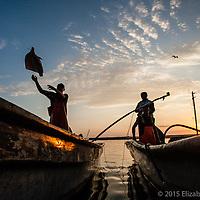 Pescadores y cargadores descargan los mantos de calamar en el muelle de Santa Rosalía al amanecer.