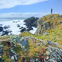 A hiker takes in the views of Malin Head, the nothern most point of Ireland. Ballyhillion, Ireland.