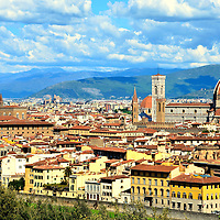 Skyline of City from Piazzale Michelangiolo in Florence, Italy<br /> In order to enjoy the beauty of Florence, you must go to the Oltrarno district. You will drive along a five mile, tree-lined boulevard called Viale dei Colli until you reach the Piazzale Michelangiolo.  From this Michelangelo Square, which was built in 1869, is a breathtaking, panoramic view of the Cathedral of Florence (right), the Palazzo Vecchio Tower (left), the city and the hills of Settignano and Fiesole.