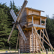 """Today's Fort Ross windmill is a full-size 1814 replica built by artisan craftsmen in Russia and reassembled in 2012 for the 200th anniversary of the fort's founding. At Fort Ross, the Russian-American Company made the first windmills in California (in 1814 and 1841), likely the first windmills west of the Mississippi River. The posttype mill (stolbovka) ground grain into flour for baking bread (for Settlement Ross and the Russians' Alaskan settlements) and also pounded tanbark for oil used in tanning leather. Fort Ross State Historic Park preserves a former Russian colony (1812-1842) on the west coast of North America, in what is now Sonoma County, California, USA. Visit Fort Ross and dramatic coastal scenery 11 miles north of Jenner on California Highway One.  Russian voyages greatly expanded California's scientific knowledge. For centuries before Europeans arrived, this site was called Metini and had been occupied by the Kashaya band of Pomo people who wove intricate baskets and harvested sea life, plants, acorns, deer, and small mammals. Sponsored by the Russian Empire, """"Settlement Ross"""" was multicultural, built mostly by Alaskan Alutiiq natives and occupied by 300-400 native Siberians, Alaskans, Hawaiians, Californians, and mixed Europeans. Renamed """"Ross"""" in 1812 in honor of Imperial Russian (Rossiia), Fortress Ross was intended to grow wheat and other crops to feed Russians living in Alaska, but after 30 years was found to be unsustainable. Fort Ross was sold to John Sutter in 1841, and his trusted assistant John Bidwell transported its hardware and animals to Sutter's Fort in the Sacramento Valley. Fort Ross is a landmark in European imperialism, which brought Spanish expanding west across the Atlantic Ocean and Russians spreading east across Siberia and the Pacific Ocean. In the early 1800s, Russians coming from the north met Spanish coming from the south along the Pacific Coast of California, followed by the USA arriving from the east in 1846 for the Mexican"""