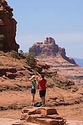Couple hiking on Broken Arrow Trail at Chicken Point, Sedona, Arizona.