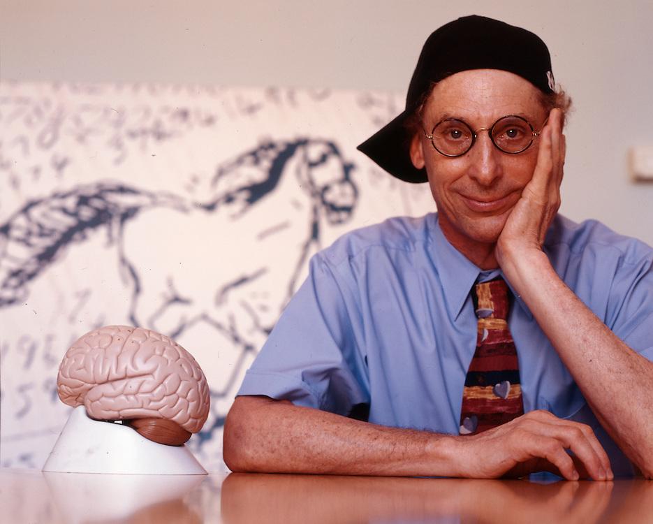 Professor Alan Snyder of The Centre for the Mind at Sydney University with his &quot;think cap&quot;. The pictures on the wall were drawn by four year old autistic children.<br /> Sydney, March 2003