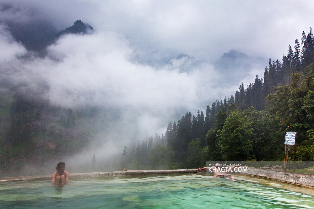 Tourists in the pool of natural hot water springs in Kheerganga, a place in Parvati valley in Kullu, Himachal Pradesh, India