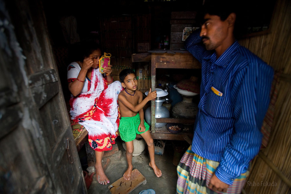Aging sex worker Josna, 60, left, applies makeup as her daughter Tanya, 7, sits by at brothel in Faridpur, Bangladesh.