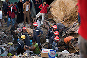 Egyptian emergency services workers help residents search for survivors amid the rubble of a giant rockslide September 06, 2008 in the Manshiyet Nasr shantytown in Cairo, Egypt. The morning rockslide officially killed 62, but that number is sure to rise as hundreds of others are believed buried under more than 70 ton giant slabs that crashed down on the slum at the bottom of unstable limestone cliffs.