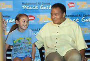 Bella Hobson, 8, a third-grade student at John F. Kennedy Montessori Elementary School, sits next to Muhammad Ali Tuesday, Sept. 21, 2010 in Louisville, Ky., as Ali and his wife Lonnie joined nearly 600 school children at Kennedy Elementary to celebrate the launch of Muhammad Ali Center Peace Gardens globally on United Nations International Day of Peace to teach children multicultural respect and nutrition through gardens. The Muhammad Ali Center and Yum! Brands Foundation partnered to launch the initiative and Yum!Brands Foundation is underwriting the initiative as an extension of its World Hunger Relief effort. (AP Photo/Brian Bohannon)