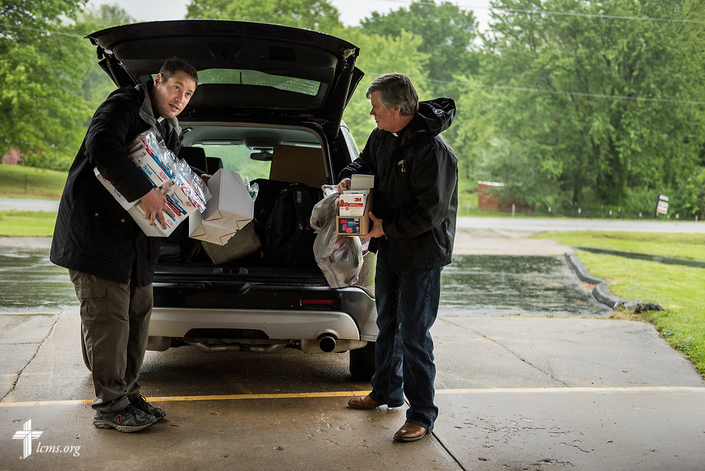 The Rev. Michael Meyer, manager of LCMS Disaster Response (left), and the Rev. Steve Gillmore, pastor of First Lutheran Church, Neosho Mo., carry protective gear for flood muck-out work at affected church member homes on Wednesday, May 3, 2017, at the parish in Neosho. LCMS Disaster Response provided for the supplies. LCMS Communications/Erik M. Lunsford