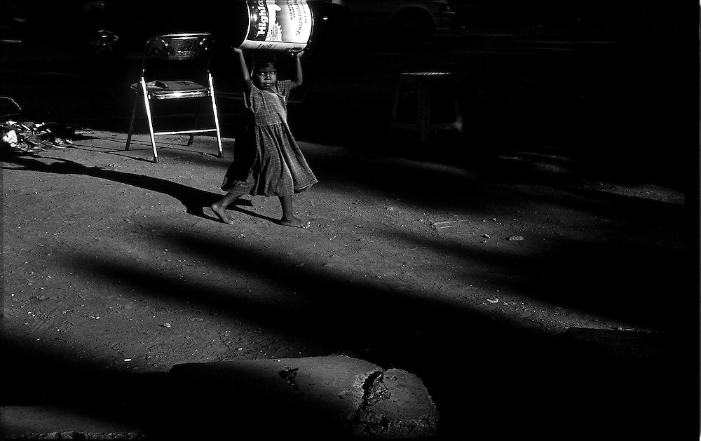 Little Girl walking in Dili with an heavy load on her head. @ Martine Perret. 17 May 2002