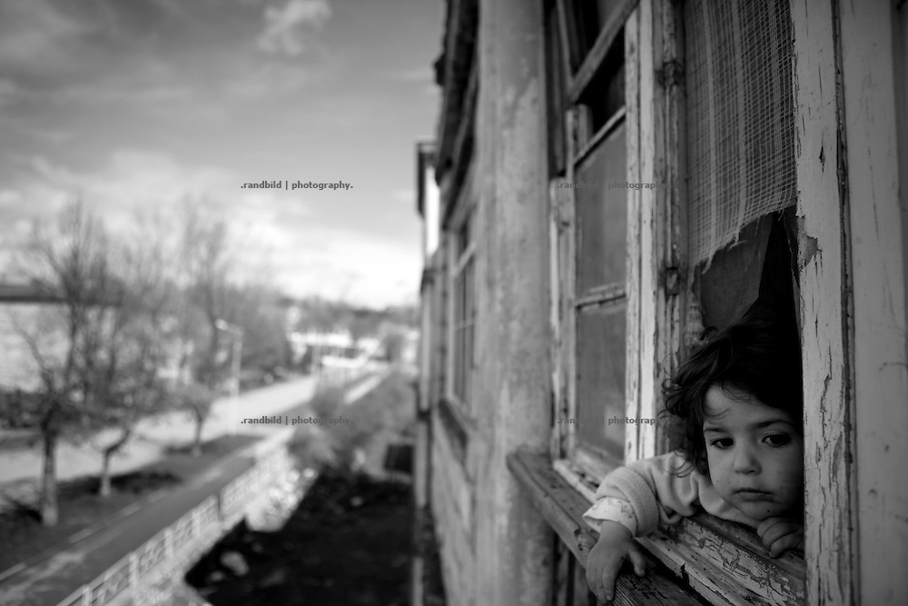 "A little girl takes a view out of a window. This image is part of the photoproject ""The Twentieth Spring"", a portrait of caucasian town Shushi 20 years after its so called ""Liberation"" by armenian fighters. In its more than two centuries old history Shushi was ruled by different powers like armeniens, persians, russian or aseris. In 1991 a fierce battle for Karabakhs independence from Azerbaijan began. During the breakdown of Sowjet Union armenians didn´t want to stay within the Republic of Azerbaijan anymore. 1992 armenians manage to takeover ""ancient armenian Shushi"" and pushed out remained aseris forces which had operate a rocket base there. Since then Shushi became an ""armenian town"" again. Today, 20 yeras after statement of Karabakhs independence Shushi tries to find it´s opportunities for it´s future. The less populated town is still affected by devastation and ruins by it´s violent history. Life is mostly a daily struggle for the inhabitants to get expenses covered, caused by a lack of jobs and almost no perspective for a sustainable economic development. Shushi depends on donations by diaspora armenians. On the other hand those donations have made it possible to rebuild a cultural centre, recover new asphalt roads and other infrastructure. 20 years after Shushis fall into armenian hands Babies get born and people won´t never be under aseris rule again. The bloody early 1990´s civil war has moved into the trenches of the frontline 20 kilometer away from Shushi where it stuck since 1994. The karabakh conflict is still not solved and could turn to an open war every day. Nonetheless life goes on on the south caucasian rocky tip above mountainious region of Karabakh where Shushi enthrones ever since centuries."