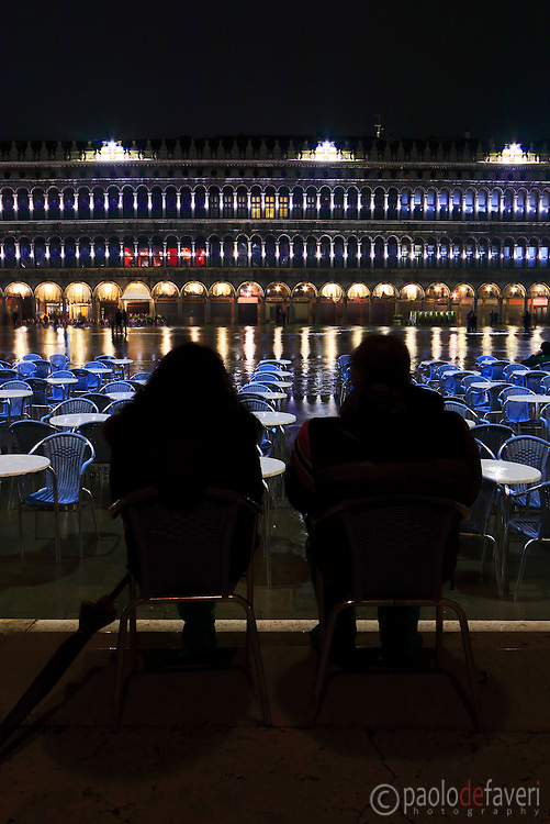 "Two people sitting on the chairs of Cafè Florian under the porticoes in San Marco square, attending the show of the ""acqua alta"" by night (high tide), completely flooding the square and most of the city of Venice"