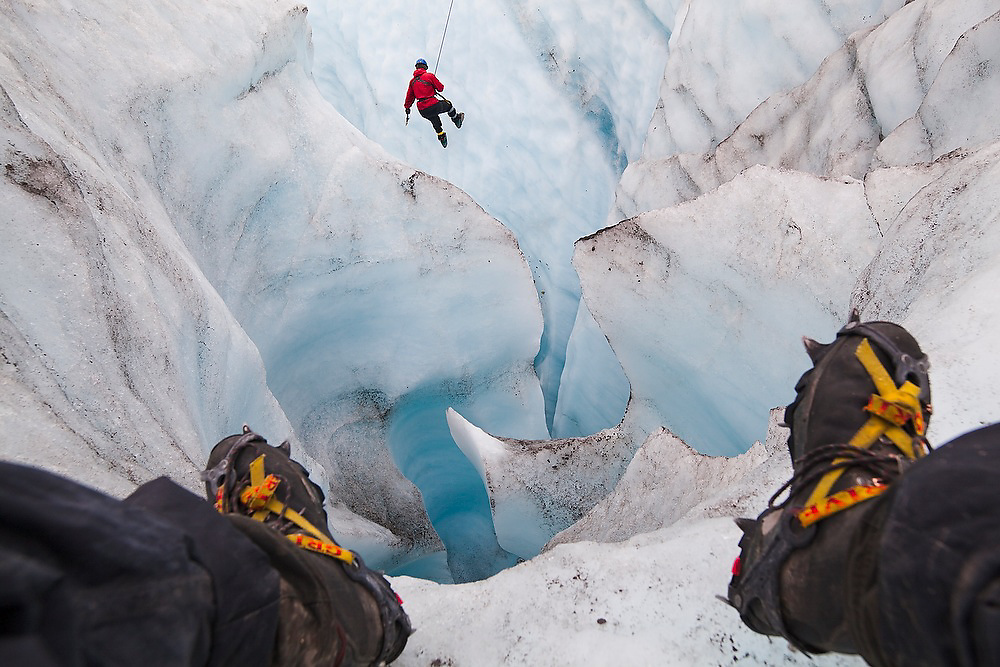 Ethan Welty sits on the edge of a deep moulin to photograph client Mack F. Pennington ice climbing (for his first time ever) on a day trip with St. Elias Alpine Guides to the Root Glacier in Wrangell-St. Elias National Park, Alaska.