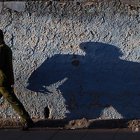 A military man's shadow is cast on a wall in Santa Clara, Cuba.
