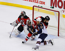 Nov 1, 2008; Newark, NJ, USA; New Jersey Devils goalie Kevin Weekes (1) makes a save while New Jersey Devils defenseman Mike Mottau (27) hits Atlanta Thrashers right wing Chris Thorburn (27)during the third period at the Prudential Center. The Devils defeated the Thrashers 6-1.