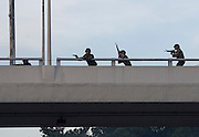 Military forces loyal to the government open fire on protesters from an overpass in Bangkok...Violence between the 'Red Shirts' of the UDD and police / government military forces on the city streets of Bangkok. The UDD (United Front for Democracy Against Dictatorship) says Prime Minister Abhisit Vejjajiva came to power illegitimately and is a puppet of the military. The movement is made up of supporters of former Prime Minister Thaksin Shinawatra who was ousted in a coup in September 2006. The UDD wants Mr Abhisit to resign and call fresh elections.