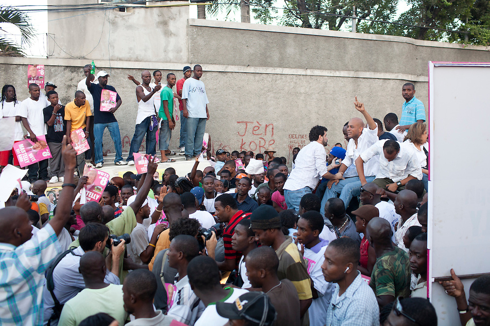 Haitian presidential candidate Michel Martelly (C) rides on top of a truck during an impromptu election protest on November 28, 2010 in Port-au-Prince, Haiti.