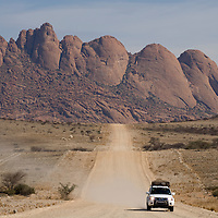 Africa, Namibia, Usakos, Safari truck drives down dirt road with Spitzkoppe mountain looming in background