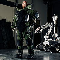 A U.S. Air Force explosive ordinance disposal team member dressed in his full bomb suite stands near his robot. The Airman uses the robot to disarm bombs remotely. Some bombs must be disarmed by a technician, so they wear bomb resistant suits.