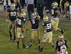 Manti Te'o (5) celebrates with linebacker Kerry Neal (56) and linebacker Brian Smith (58) after a quarterback sack in the fourth quarter of the final home game upset of Utah in 2010.